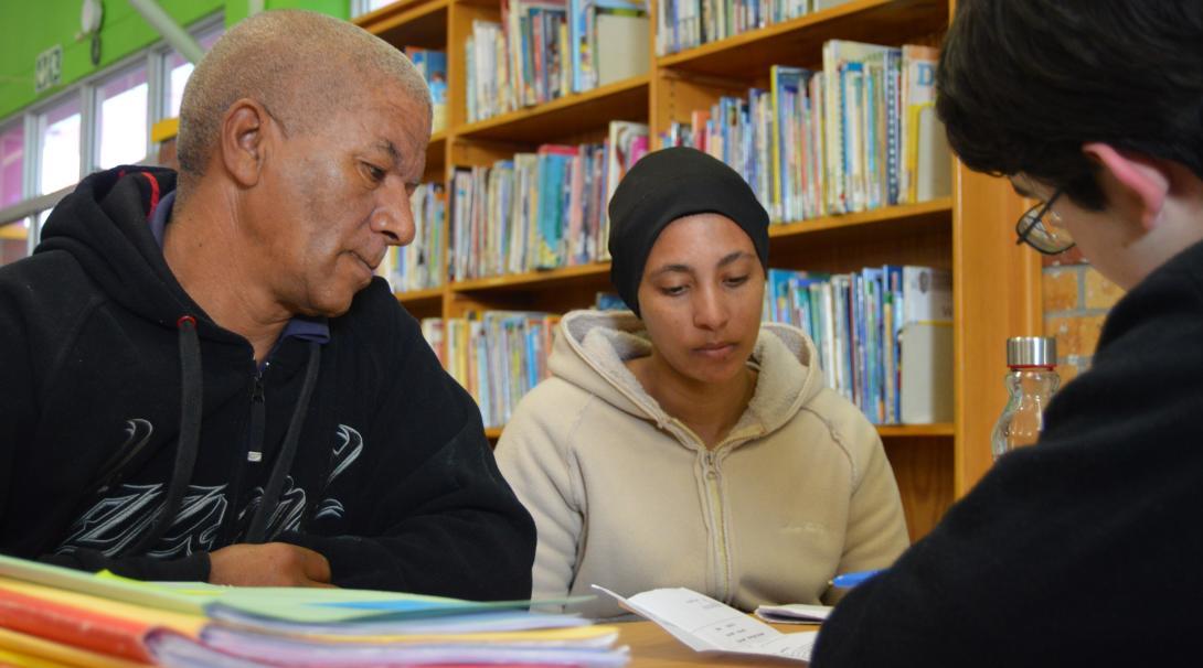 Un pasante de derechos humanos asesorando a una familia.